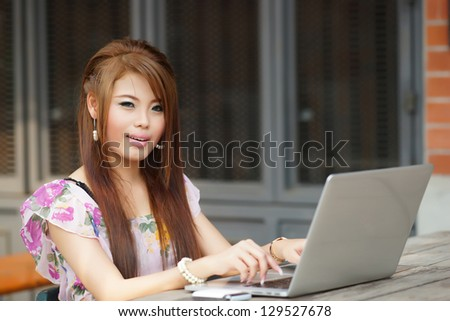Young attractive business woman working on her laptop at outdoors cafe