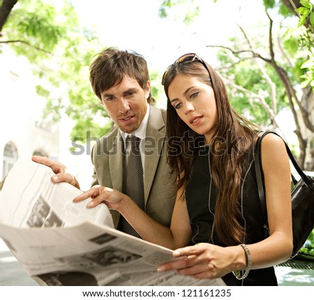 Young attractive businessman and businesswoman standing together and sharing a newspaper in a tree aligned street in a classic city, smiling.