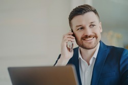 Young attractive businessman in formal suit talking on phone and smiling when hearing good news. Happy manager sitting in office in front of laptop and thinking of positive outcomes of conversation