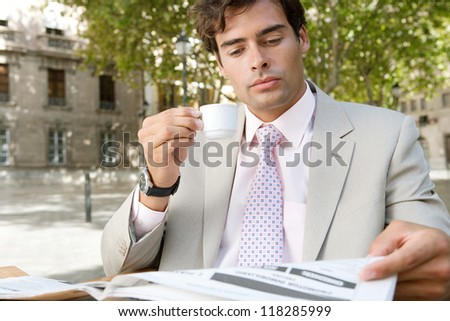 Young attractive businessman reading the newspaper while sitting at a coffee shop terrace table, outdoors, in a classic city square with trees.