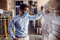 Young attractive businessman wearing protective sterile mask and checking out packed goods.