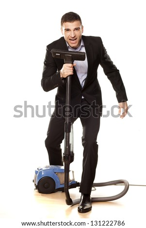Young attractive businessman with a vacuum cleaner