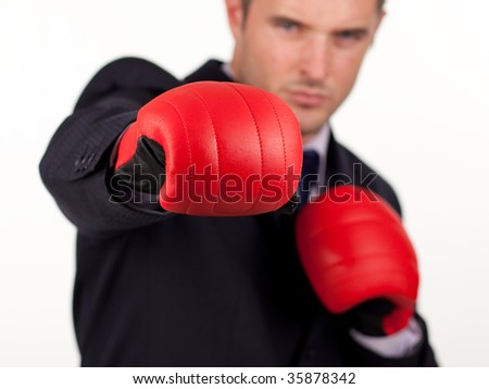 Young attractive businessman with boxing gloves and focus on gloves