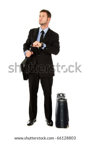 Young attractive businessman with briefcase and suitcase impatient checking the time. Looking forward to go. Studio shot. White background.