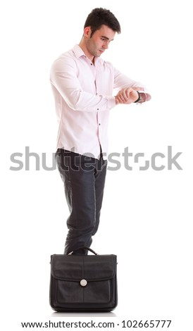 Young attractive businessman with briefcase impatient checking the time. Studio shot. White background.