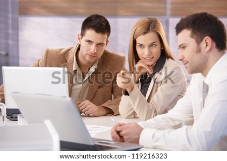 Young attractive businesspeople teamworking in meeting room.