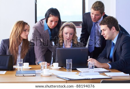 Young attractive businesswoman and her team, sitting at conference table and work on laptop computer