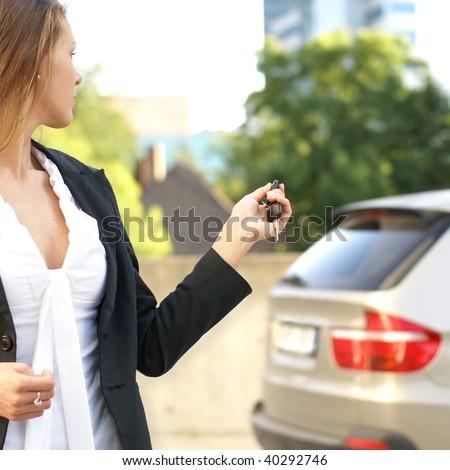 Young attractive businesswoman closes the door of her car