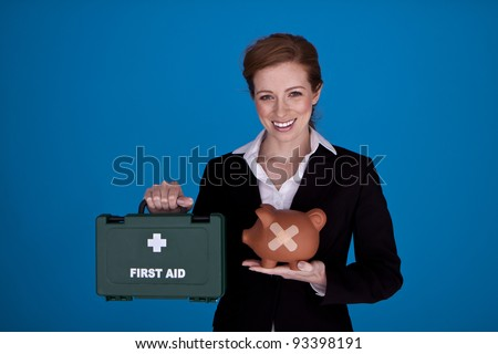 Young attractive businesswoman holding a piggybank and first aid kit as a money recovery concept. Fixing the banking crises.