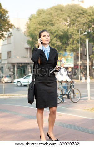 young attractive businesswoman on the phone walking on street, concept-city woman