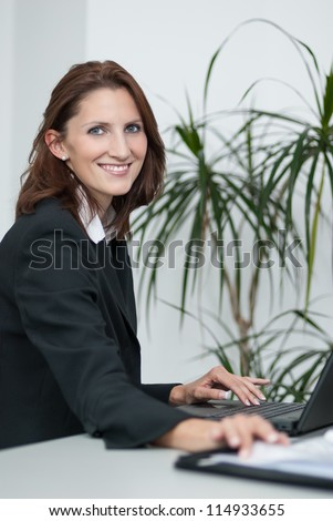 Young attractive businesswoman sits in the office at a table and uses her laptop