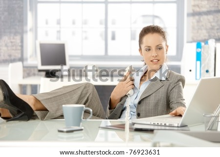 Young attractive businesswoman sitting at desk in bright office, holding away phone while checking information on laptop, resting legs on top of desk.?