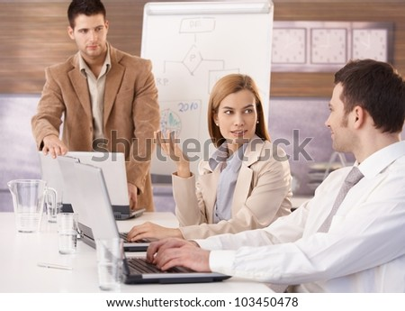 Young attractive businesswoman sitting at meeting with colleagues.