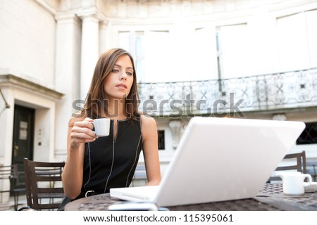 Young attractive businesswoman sitting in a luxurious coffee shop terrace with her laptop, holding a cup of coffee.