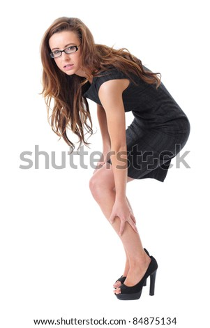 Young attractive businesswoman suffer from pain in her leg, isolated on white