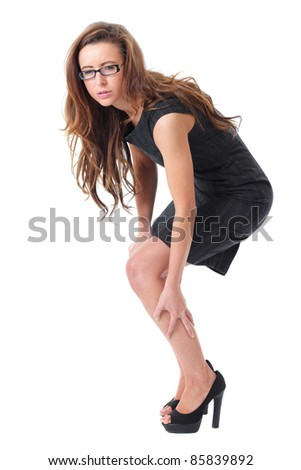 Young attractive businesswoman suffer from pain in her leg, isolated on white - stock photo