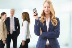 Young attractive businesswoman talking on mobile phone in office, her colleagues on the background