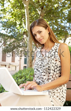 Young attractive businesswoman using a pc laptop computer while sitting on a wooden bench in a city park.