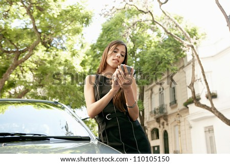 Young attractive businesswoman using a smart phone while leaning on a shiny car in a classic business street.