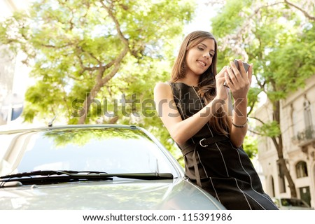 Young attractive businesswoman using her smart phone while leaning on a car in a tree lined street, outdoors.