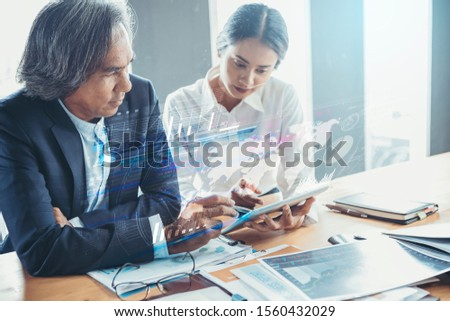 Young attractive businesswoman working with touchpad has been guided and consulting by senior colleague with visual graphic