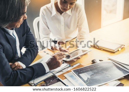 Young attractive businesswoman working with touchpad has been guided and consulting by senior colleague