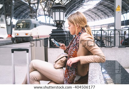 young attractive businesswoman writes a text message while waiting for the train. attractive young blonde woman using smart-phone while sitting on the railway station platform