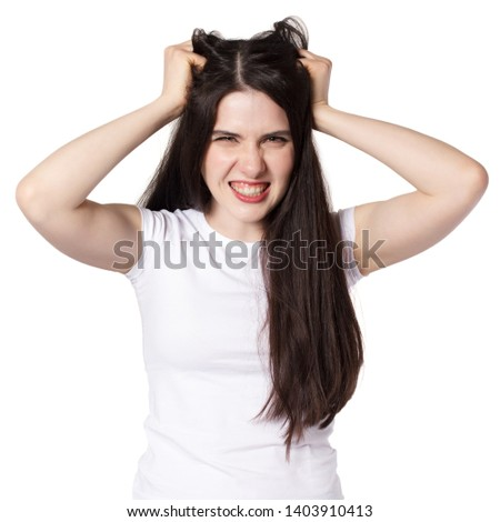 Young attractive caucasian black haired brunette woman in white t shirt, hands grabed and pulling her hair, anger woman concept idea #1403910413