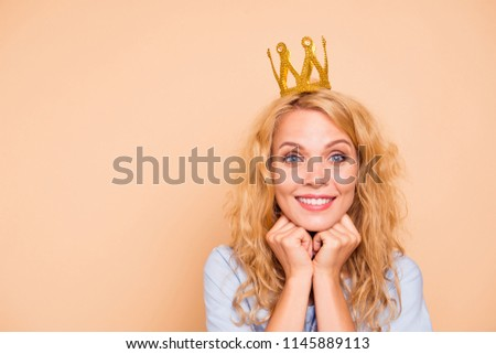 Young attractive caucasian curly-haired gorgeous cheerful sweet smiling happy woman wearing golden crown and blue dress. Isolated over pastel yellow background, copy space