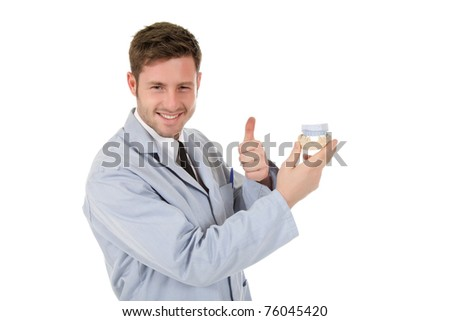 Young attractive caucasian male doctor dentist holding a plaster cast and gesturing thumb up. Studio shot. White background
