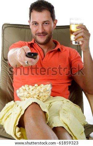 Young attractive caucasian man sitting on sofa with popcorn and holding a glass of beer and a remote control. Studio shot. White background.