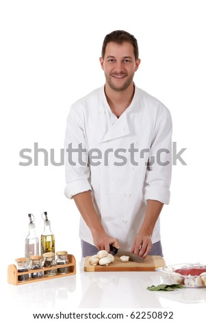 Young attractive chef caucasian male with uniform cutting fresh mushrooms for a tasty roast beef. Studio shot. White background.