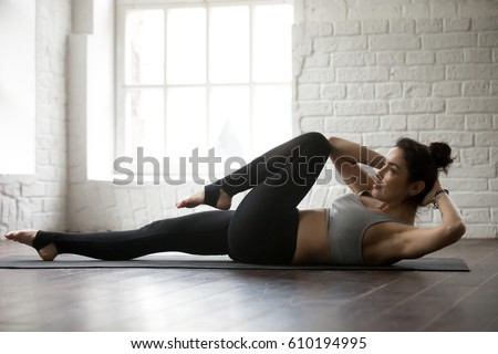 Young attractive cool sporty woman doing crisscross fitness exercise, bicycle crunches, working out on the floor, wearing black sportswear bra and black pants, full length white loft studio background #610194995