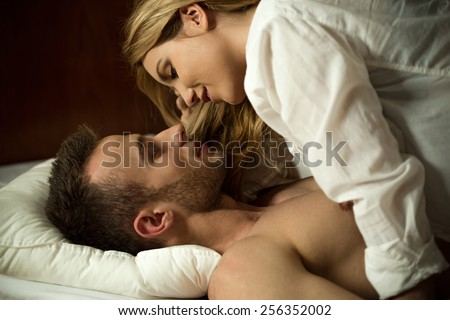 Young attractive couple in love hugging in bed