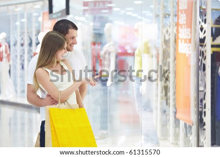 Young attractive couple in shop window