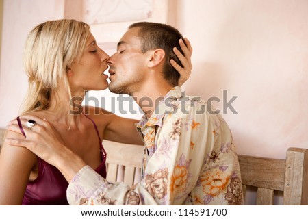 Young attractive couple intensely kissing while sitting down on a bench on honeymoon.