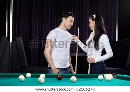 Young attractive couple near to a billiard table