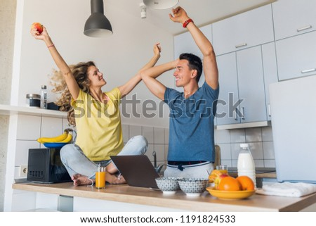young attractive couple of man and woman cooking breakfast together in morning at kitchen, happy family, romantic, healthy food, freelancer at work on laptop, dancing to music, having fun, laughing #1191824533