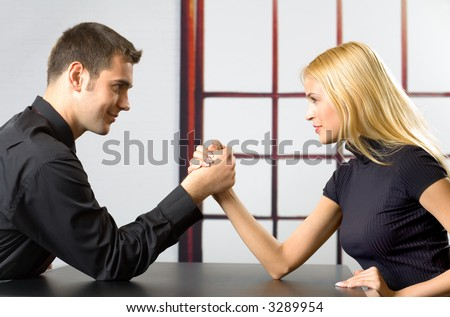 Young attractive couple or business people fighting in arm-wrestling