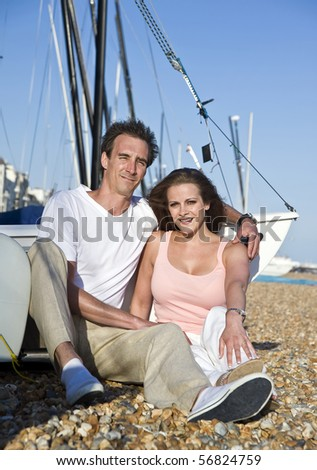 Young attractive couple relaxing on beach with boats in background