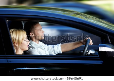 Young attractive couple riding in a car - stock photo