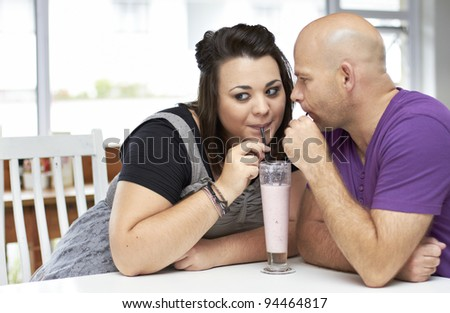 Young attractive couple sharing a milkshake
