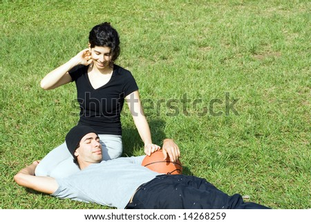 Young, attractive couple sitting together on a grassy field.  The man is laying across the woman's lap and holding up a basketball.  Horizontally framed shot.