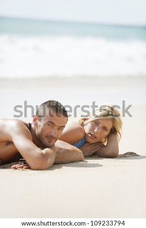 Young attractive couple sunbathing on a beach by the shore while on vacation.