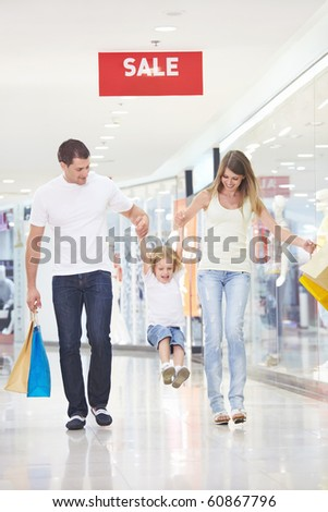 Young attractive couple with a child in the store