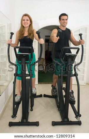 Young, attractive couple working out at the gym together. Vertically composed shot taken from directly in front of the couple.
