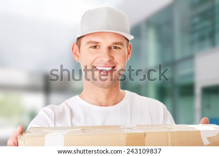 Young attractive courier guy delivering brown box
