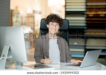 Young attractive curly designer making notes in front of laptop