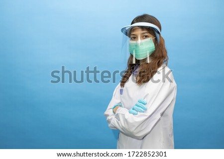 young attractive dentist wearing surgical mask and face shield. the written on her gown is he name in Thai alphabets Stock photo ©