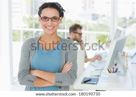 Young attractive designer smiling at camera in creative office